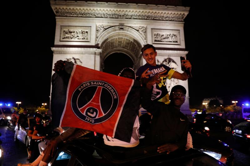Paris Saint-Germain supporters celebrate their team's 3-0 win over RB Leipzig at the Champs-Elysees Avenue near the Arc de Triomphe in Paris on late August 18, 2020 following the UEFA Champions League semi-final football match between Leipzig and Paris Saint-Germain, played in Lisbon. - Paris Saint-Germain are through to the final of the Champions League for the first time after goals by Marquinhos, Angel Di Maria and Juan Bernat saw them ease to a 3-0 win over RB Leipzig in a one-sided semi-final in Lisbon on August 18. (Photo by GEOFFROY VAN DER HASSELT / AFP) (Photo by GEOFFROY VAN DER HASSELT/AFP via Getty Images)