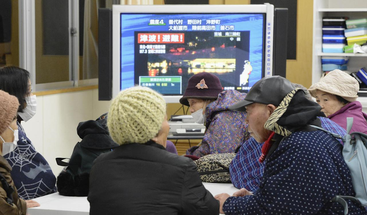 Tsunami evacuees watch TV news flashing a tsunami warning at their shelter Takata Junior High School that stands on a higher ground in Rikuzentakata in Iwate Prefecture, Friday, Dec. 7, 2012 after a strong earthquake struck off the coast of northeastern Japan. It is the same region that was hit by a massive earthquake and tsunami last year. (AP Photo/Kyodo News) JAPAN OUT, MANDATORY CREDIT, NO LICENSING IN CHINA, FRANCE, HONG KONG, JAPAN AND SOUTH KOREA