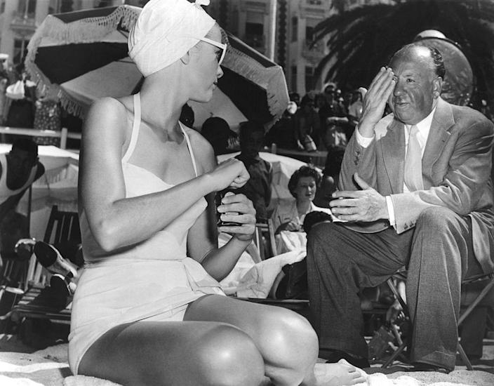 <p>Kelly receives notes from her <em>To Catch a Thief </em>director, Alfred Hitchcock, as she films a scene on the beach in 1955. </p>