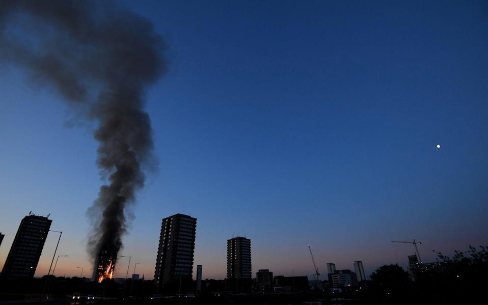 Flames and smoke can be seen in the distance from the Latimer Road block of flats - Credit: Reuters
