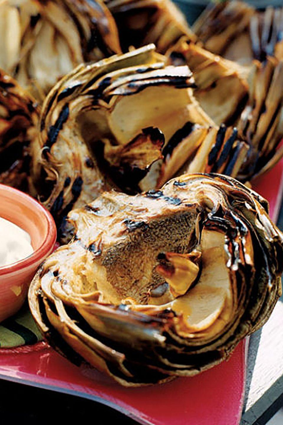 "<p>Believe it or not, artichokes can look as scrumptious as they taste, especially with this mouthwatering recipe.</p><p><strong><a href=""https://www.countryliving.com/food-drinks/recipes/a1216/grilled-artichokes-creamy-butter-dip-3322/"" rel=""nofollow noopener"" target=""_blank"" data-ylk=""slk:Get the recipe"" class=""link rapid-noclick-resp"">Get the recipe</a>.</strong><br></p><p><a class=""link rapid-noclick-resp"" href=""https://www.amazon.com/Hamilton-Beach-25361-Removable-Stainless/dp/B00KLVY3TW/?tag=syn-yahoo-20&ascsubtag=%5Bartid%7C10063.g.35089489%5Bsrc%7Cyahoo-us"" rel=""nofollow noopener"" target=""_blank"" data-ylk=""slk:SHOP INDOOR GRILLS"">SHOP INDOOR GRILLS</a></p>"