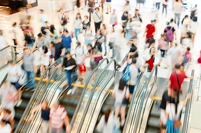 A blurred image of dozens of shoppers moving up and down the escalator