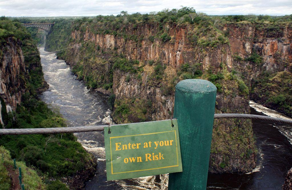 Victoria Falls, Zimbabwe: A sign warns tourists from proceeding from a lookout point over the Zambezi River below Victoria Falls, Zimbabwe. Called one of the world's seven natural wonders, Victoria Falls stretches 1708 meters, forming the world's largest waterfall.