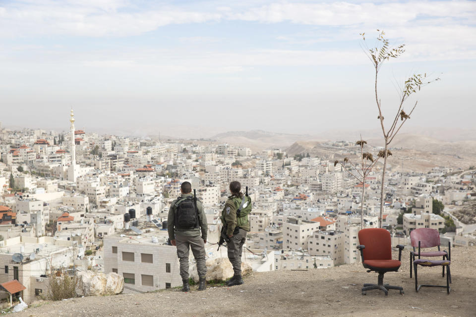 FILE - In this Dec. 10, 2017 file photo, Israeli border police officers look over the Arab neighborhood of Issawiyah in Jerusalem. A dispute over Israeli restrictions on Palestinian voters in east Jerusalem is threatening to cancel or delay the first Palestinian elections in more than 15 years. (AP Photo/Oded Balilty, File)
