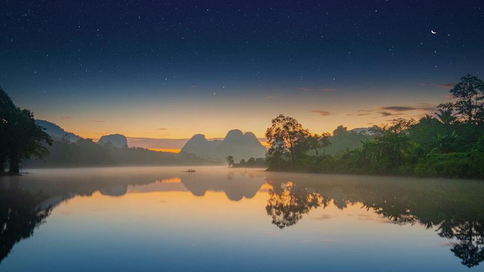 <p>A slight mist comes over a lake in Krabi Province as the sun begins to rise in Thailand.</p>