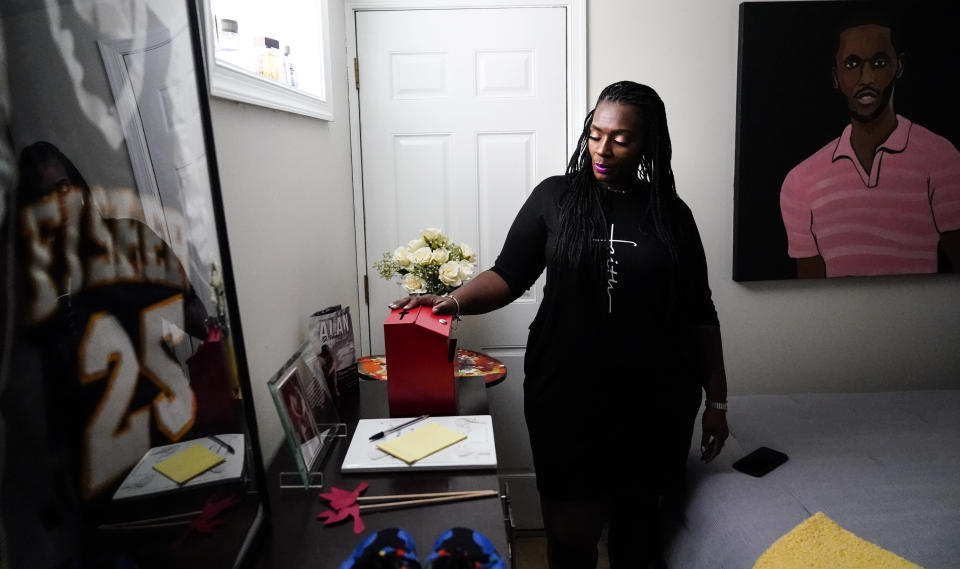 In this July 8, 2021, photo Latrice Felix whose son Alan Womack Jr. was was killed in 2020 during a fight, places her hand on a box she leaves notes to him in, during an interview with The Associated Press in King of Prussia, Pa. (AP Photo/Matt Rourke)