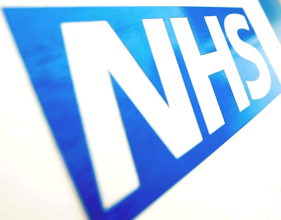 """File photo dated 06/11/10 of the NHS logo. The record number of patients waiting for hospital treatment shows the """"calamitous impact"""" of coronavirus on waiting times in England, a leading surgeon has said. New figures published on Thursday show that a total of 4.46 million people were waiting to start hospital treatment in England at the end of November 2020, the highest number since records began."""