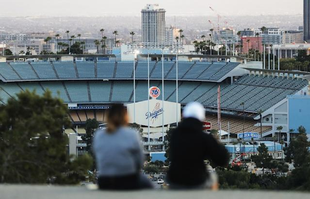 "People sit on a hill overlooking Dodger Stadium on what was supposed to be Major League Baseball's opening day, March 26. <span class=""copyright"">(Mario Tama / Getty Images)</span>"