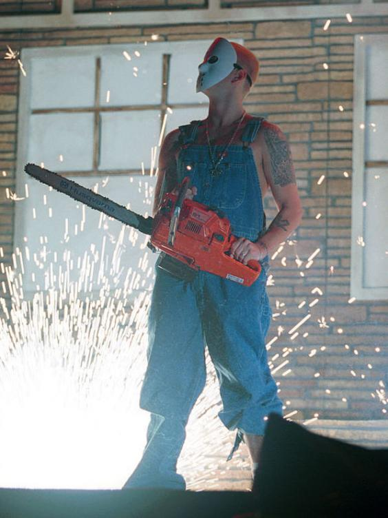 Eminem sports a Jason Voorhees mask and chainsaw in concert in October 2000 (George DeSota/Newsmakers)