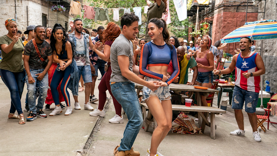 Usnavi and Vanessa dance outside while a crowd of friends watches them cheerfully.