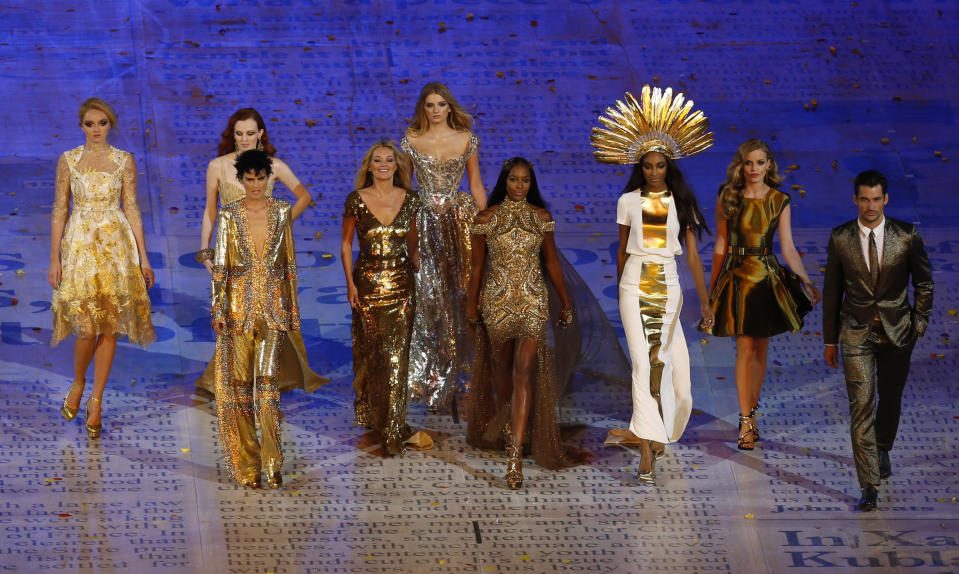 """FILE - This Sunday Aug. 12, 2012 file photo shows models, from left, Lily Cole, Karen Elson, Stella Tennant, Kate Moss, Lily Donaldson, Naomi Campbell, Jourdan Dunn and Georgia May Jagger walking with male model David Gandy during the Closing Ceremony at the 2012 Summer Olympics in London. Tennant, the aristocratic British model who was a muse to designers including Karl Lagerfeld and Gianni Versace, has died suddenly at the age of 50, her family said Wednesday, Dec. 23, 2020. The family asked for their privacy to be respected and said Tennant was """"a wonderful woman and an inspiration to us all."""" Police Scotland said there were no suspicious circumstances. (AP Photo/Alastair Grant, File)"""
