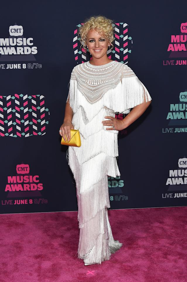 <p>The singer, known for her fun fashion choices, looked back to the '20s for her white fringed gown, which she paired with a yellow envelope clutch. <i>(Photo: Getty Images)</i></p>