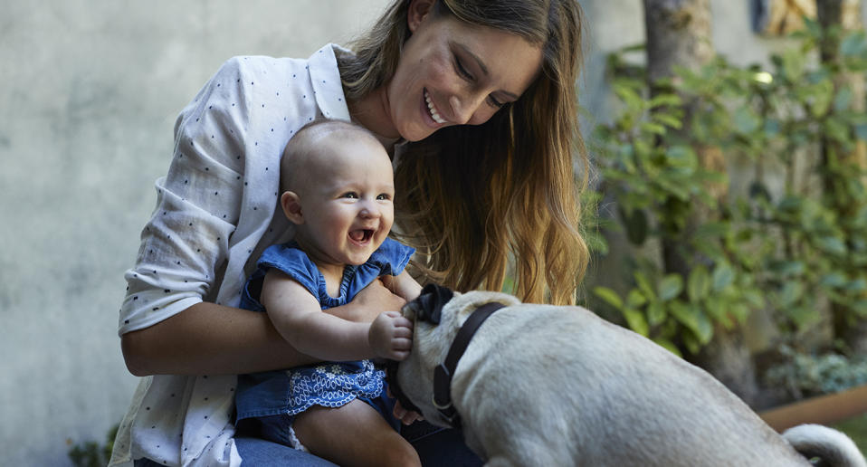 A woman and a baby play with a dog. Source: Getty Images