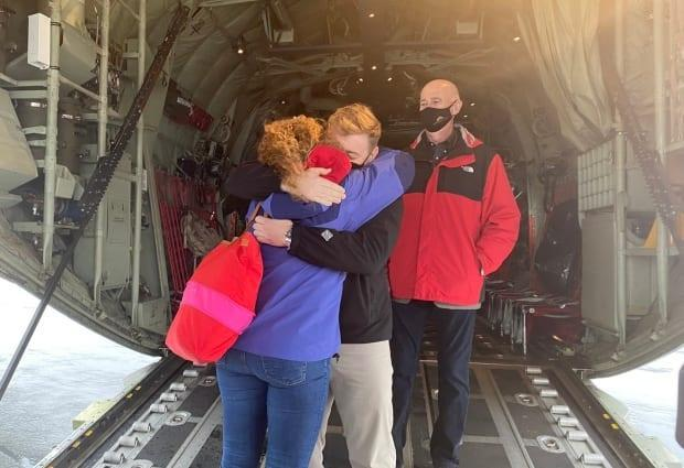 Premier Andrew Furey gives Dr. Allison Furey, his wife, a goodbye hug as she and colleagues prepare to leave St. John's for a mission to relieve exhausted colleagues in downtown Toronto hospitals.  (Andrew Furey/Twitter - image credit)