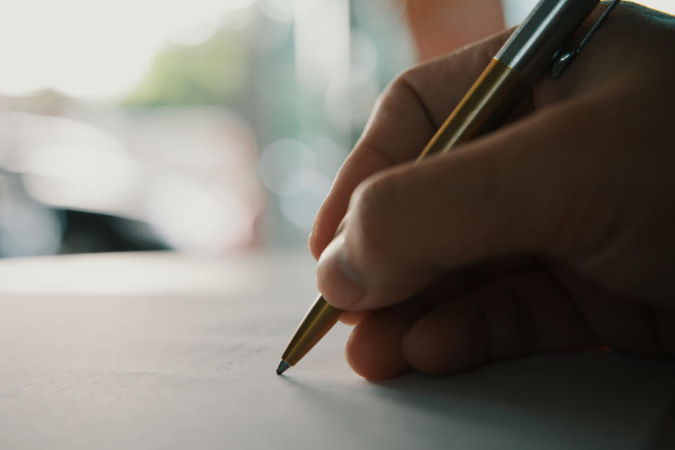 Businessman holding pen writing on paper for new appointments information in organizer concept, male hands making notes in personal paper planner at desk, close up view