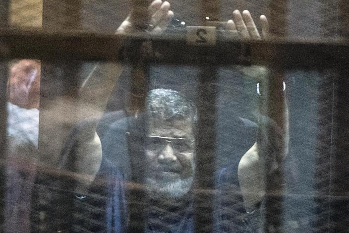 Egypt's deposed Islamist president Mohamed Morsi raises his hands from behind the defendant's cage as the judge reads out his verdict sentencing him to death at the police academy in Cairo on May 16, 2015 (AFP Photo/Khaled Desouki)