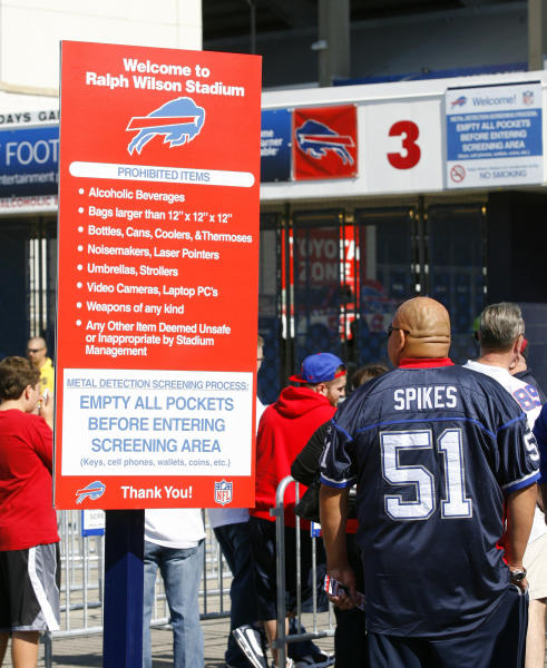 FILE - In this Sept. 16, 2012, file phot, a Buffalo Bills' fans read the security screening sign at a security checkpoint before entering the stadium for an NFL football game against the Kansas City Chiefs in Orchard Park, N.Y. The NFL is tightening stadium security starting this preseason, limiting the size and type of bags fans can bring to the game. The restrictions are designed to enhance security while speeding up entry into stadiums. (AP Photo/Bill Wippert, File)