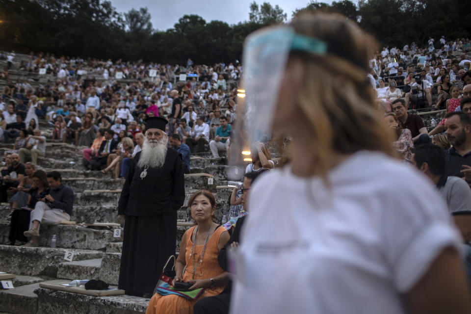 A steward wearing plastic visor stands in front of a Greek Orthodox priest as spectators take their seats at the ancient theater of Epidaurus, Greece, on Friday, July 17, 2020 Greek Culture Ministry allowed the ancient theaters of Epidaurus in southern Greece and Herodes Atticus in Athens to host performances under strict safety guidelines due the COVID-19 pandemic.(AP Photo/Petros Giannakouris)