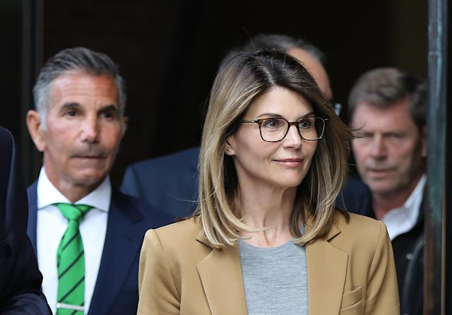 Actress Lori Loughlin and her husband Mossimo Giannulli, wearing green tie at left, leave the John Joseph Moakley United States Courthouse in Boston on April 3, 2019. (Photo by Pat Greenhouse/The Boston Globe via Getty Images)