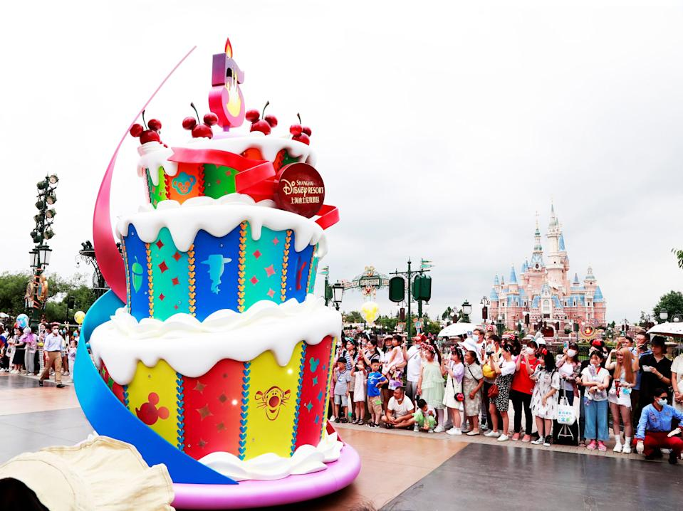this image shows a cake installation at disneyland shanghai with crowds of people lined up behind it and a castle in the background