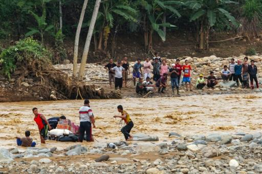 Indonesian villagers use inner tubes to deliver supplies across a river at Banjar Irigasi in Lebak, Banten province