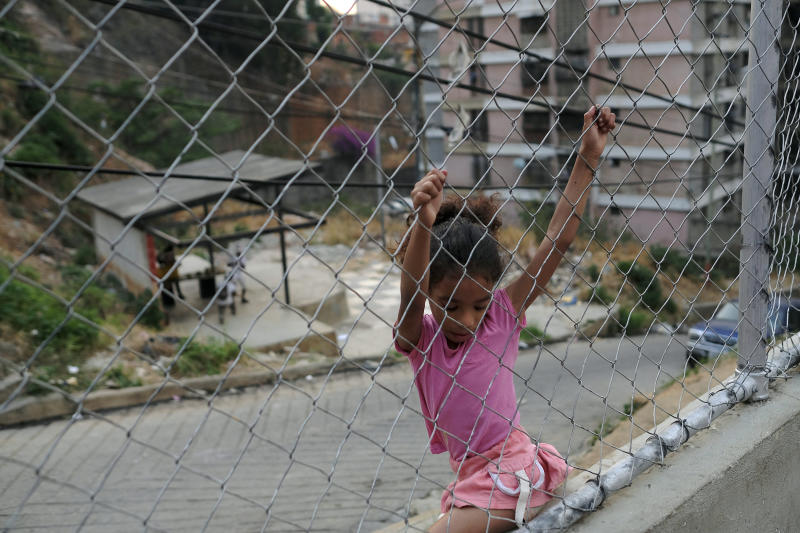 A child plays on a grid in the San Agustin neighborhood of Caracas, Venezuela, Saturday, May 16, 2020. President Nicolas Maduro is relaxing quarantine measures over the weekend by allowing children and older adults out of their homes for a few hours each day. (AP Photo/Matias Delacroix)