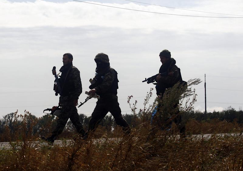 Ukrainian soldiers walk near a checkpoint on September 10, 2014, near the small eastern city of Slavyanoserbsk