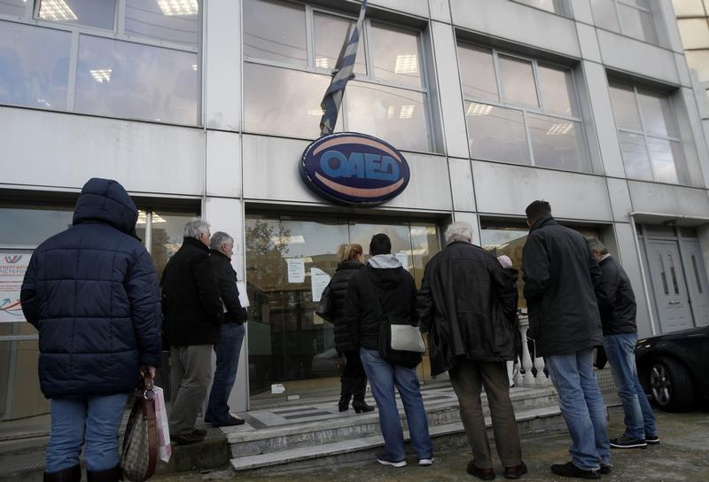 People wait outside OAED office in an Athens suburb