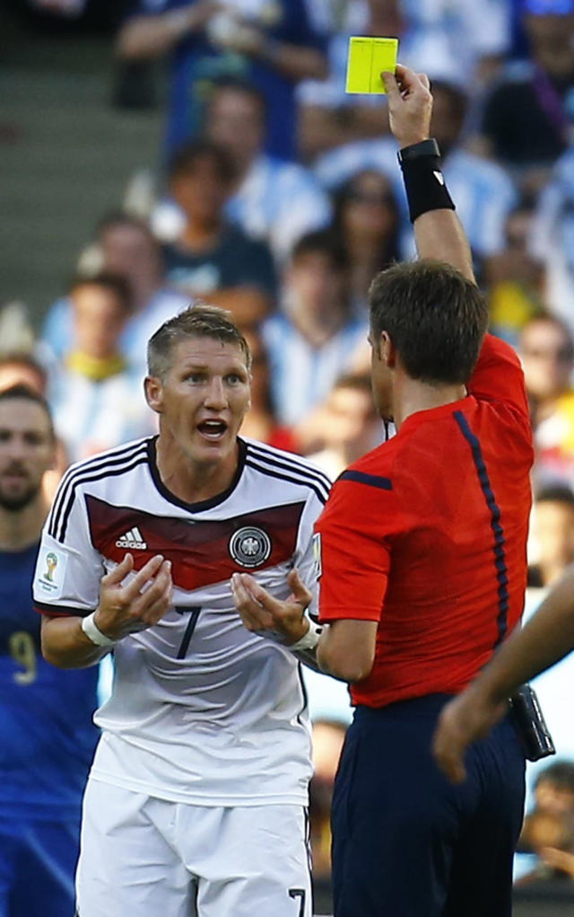 Germany's Bastian Schweinsteiger reacts as he is shown the yellow card by referee Nicola Rizzoli of Italy (R) during the 2014 World Cup final between Germany and Argentina at the Maracana stadium in Rio de Janeiro July 13, 2014. REUTERS/Kai Pfaffenbach (BRAZIL - Tags: SOCCER SPORT WORLD CUP)