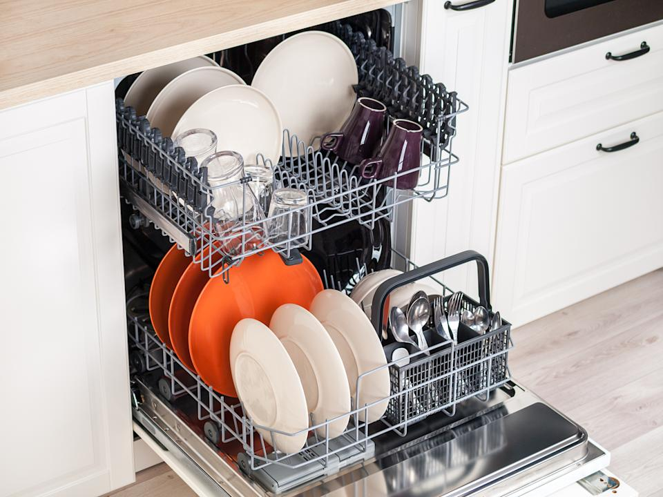 built-in kitchen dishwasher with an open door and clean, washed dishes, ease of use, saving time and water consumption when using modern dishwashers, eco friendly