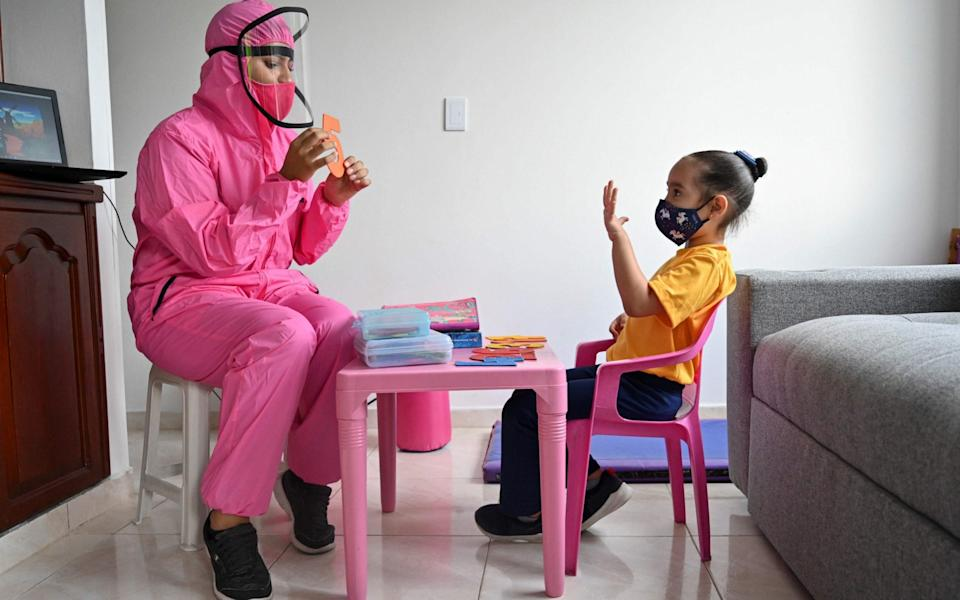 A teacher wearing a biosecurity suit gives a class to a girl at home in Cali, Colombia - AFP