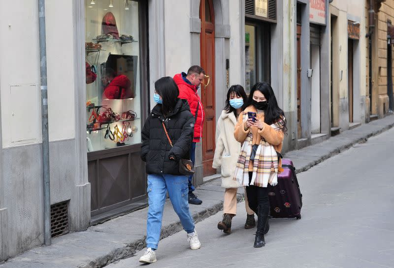 FILE PHOTO: People wearing protective masks walk through the street of Florence as Italy battles a coronavirus outbreak