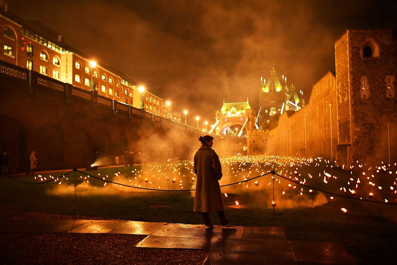 <p>A visitor is seen amongst lit torches, part of the installation 'Beyond the Deepening Shadow' at the Tower of London, in London, Britain, November 7, 2018. (Photo from Reuters/Dylan Martinez) </p>