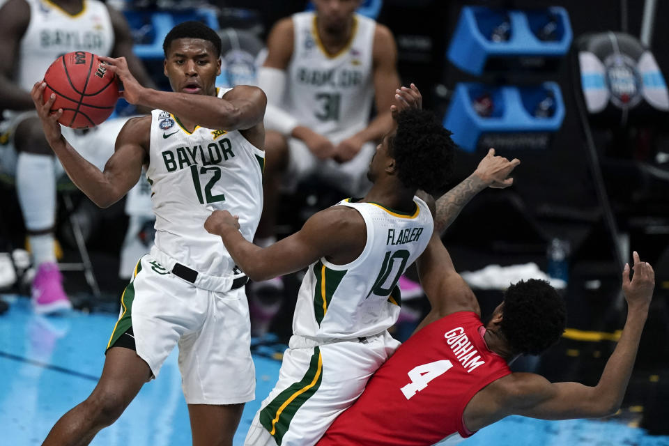 Baylor's Jared Butler (12) passes over teammate guard Adam Flagler (10) and Houston forward Justin Gorham (4) during the first half of a men's Final Four game on April 3. (AP)