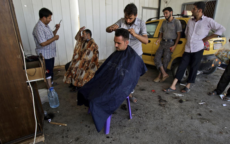 Syrian barbers, who fled their homes, due to fighting between the Syrian army and the rebels, shave the heads of other displaced men, as they take refuge at the Bab Al-Salameh border crossing, in hopes of entering one of the refugee camps in Turkey, near the Syrian town of Azaz, Sunday, Sept. 2, 2012. (AP Photo/Muhammed Muheisen)