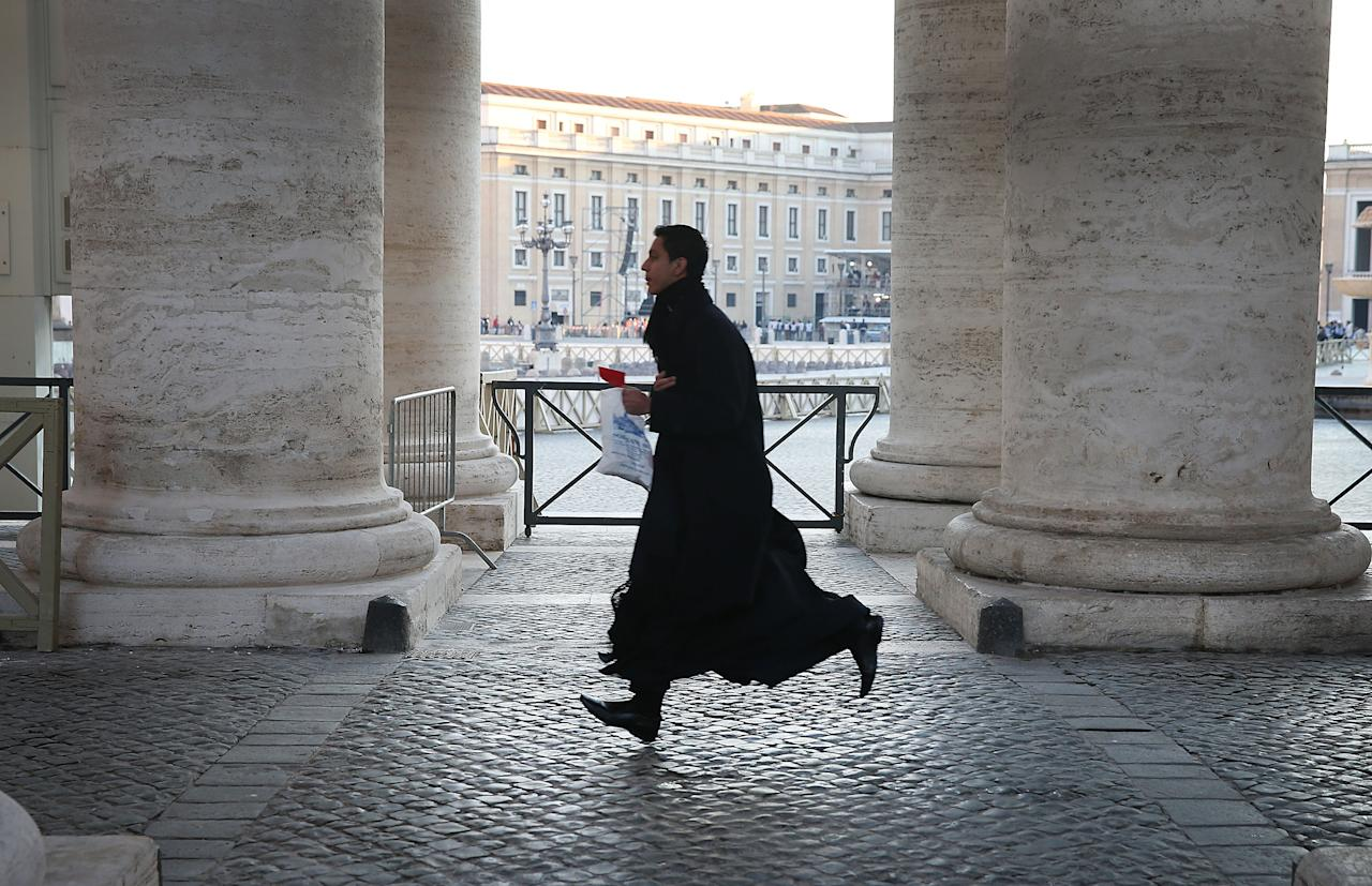 VATICAN CITY, VATICAN - FEBRUARY 27:  A priest runs to get into St Peter's Square ahead of Pope Benedict XVI's last public audience on February 27, 2013 in Vatican City, Vatican.  The Pontiff will hold his last weekly public audience later before he abdicates tomorrow. Pope Benedict XVI has been the leader of the Catholic Church for eight years and is the first Pope to retire since 1415. He cites ailing health as his reason for retirement and will spend the rest of his life in solitude away from public engagements.n  (Photo by Peter Macdiarmid/Getty Images)