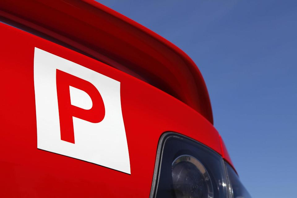 A red P plate stuck on the back of a car