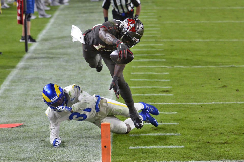 Tampa Bay Buccaneers wide receiver Chris Godwin (14) reaches for the goal line after leaping over Los Angeles Rams defensive back Darious Williams (31) for a touchdown during the second half of an NFL football game Monday, Nov. 23, 2020, in Tampa, Fla. (AP Photo/Jason Behnken)