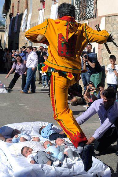 BURGOS, SPAIN - JUNE 10:  A man representing the devil leaps over babies during the festival of El Colacho on June 10, 2012 in Castrillo de Murcia near Burgos, Spain. The festival, held on the first Sunday after Corpus Cristi, represents the devil taking away original sin from the newly born babies by leaping over them.  (Photo by Denis Doyle/Getty Images)