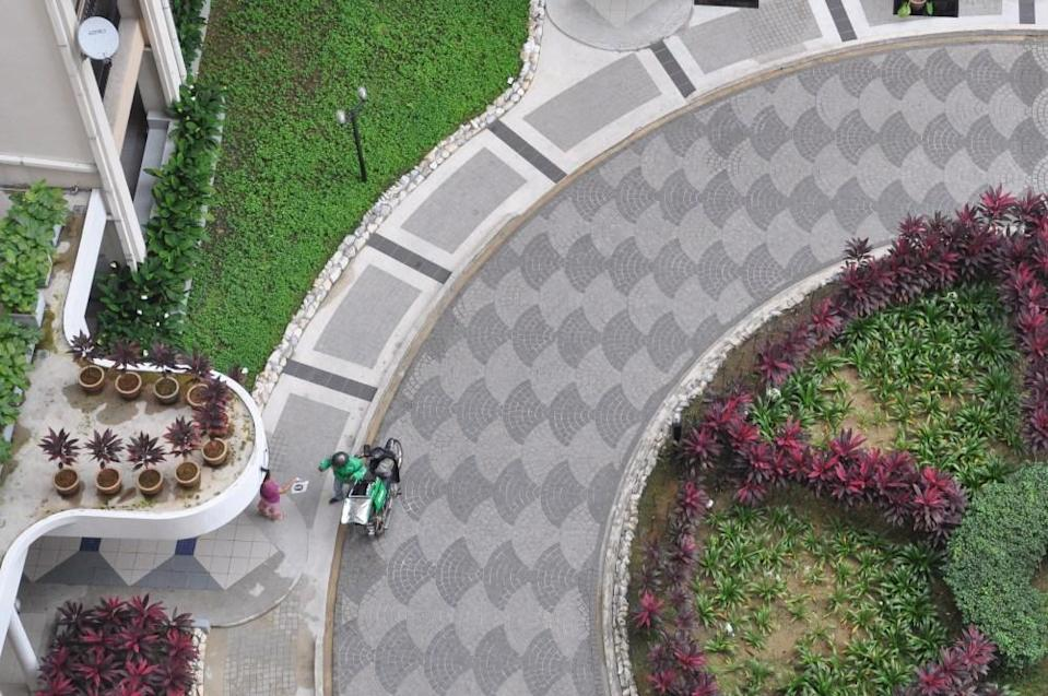 Aerial view of a delivery person, in green, sending food to a customer. Photo: Coconuts