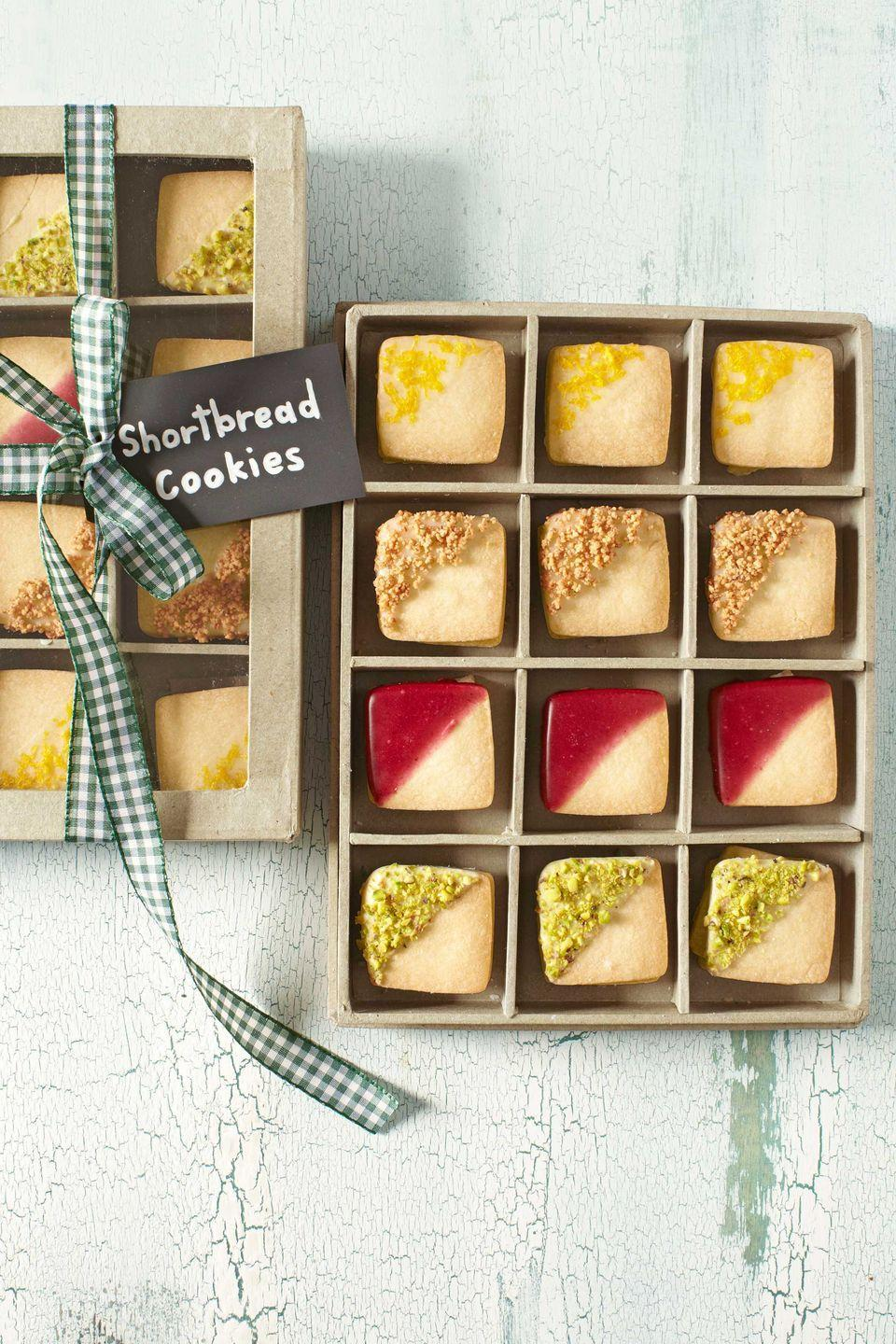 "<p>Displayed in a clear-topped checkerboard box, bite-size shortbread cookies—dipped in fruity glazes, chopped nuts, and citrus zest—pass for tiny works of art. Bonus: The sturdy container can later hold other petite treasures like jewelry or sewing notions.</p><p><strong><a href=""https://www.countryliving.com/food-drinks/recipes/a4224/shortbread-cookies-recipe-clv1212/"" rel=""nofollow noopener"" target=""_blank"" data-ylk=""slk:Get the recipe."" class=""link rapid-noclick-resp"">Get the recipe.</a></strong></p>"