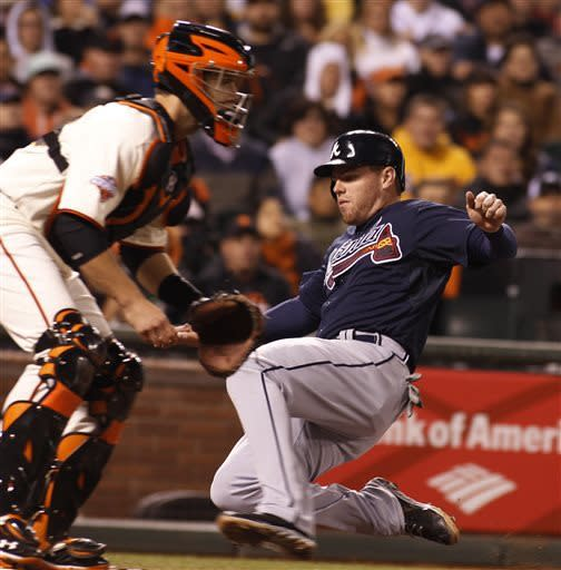Atlanta Braves' Freddie Freeman, right, scores behind San Francisco Giants' Buster Posey during the fifth inning of a baseball game, Thursday, May 9, 2013 in San Francisco. (AP Photo/George Nikitin)