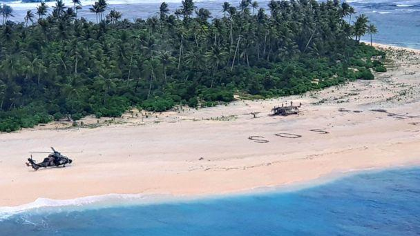 PHOTO: An Australian Army ARH Tiger helicopter lands near the letters 'SOS' on a beach on Pikelot Island where three men were found in good condition after being missing for three days, Aug. 2, 2020. (Australian Defense Force)