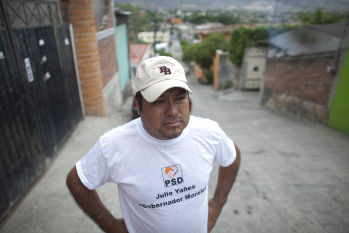 In this photo taken on Thursday, June 21, 2012, mayoral candidate Saul Garcia stands in front of his home, weeks after men on a motorcycle shot his front gate and left a message on the behalf of a drug cartel warning him to withdraw from the race or the gang would kill him and his family, in Emiliano Zapata, Morelos. As Mexicans head to the ballot box Sunday, drug cartels are registering their votes with scare tactics and cold, hard cash to make sure whoever is elected doesn't interfere with their lucrative operations. (AP Photo/Alexandre Meneghini)