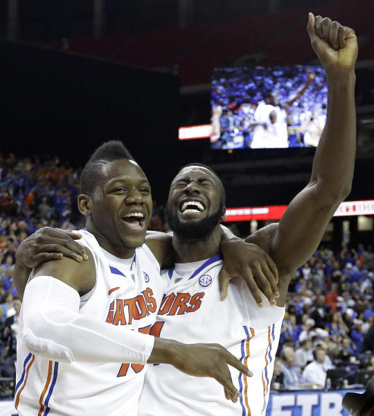 Florida's forward Will Yeguete (15) Patric Young (4) celebrate after the second half of an NCAA college basketball game against Kentucky in the Championship round of the Southeastern Conference men's tournament, Sunday, March 16, 2014, in Atlanta. Florida won 61-60. (AP Photo/Steve Helber)