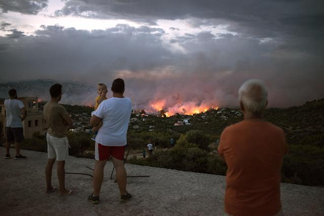 <p>People watch a wildfire in the town of Rafina, near Athens, on July 23, 2018. (Photo: Angelos Tzortzinis/AFP/Getty Images) </p>