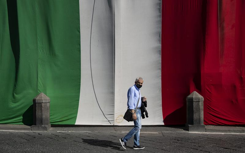 A man walks by the Italian flag displayed on a building in Naples, Italy - Ivan Romano/Getty Images