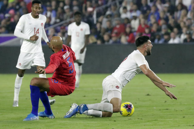 United States midfielder John Brooks (5) and Canada forward Lucas Cavallini, right, fall after they collided while going for the ball during the first half of a CONCACAF Nations League soccer match Friday, Nov. 15, 2019, in Orlando, Fla. (AP Photo/John Raoux)