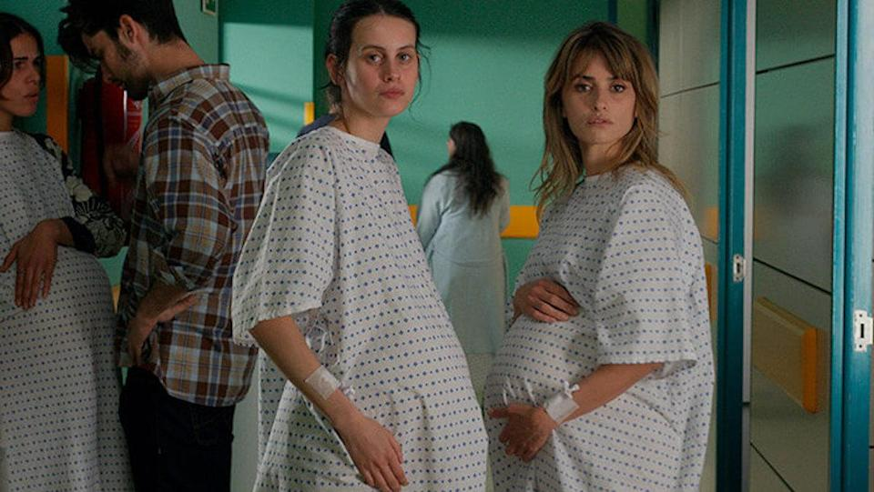 Ana and Janis, both very pregnant, stand in the hallway of a maternity ward in a hospital