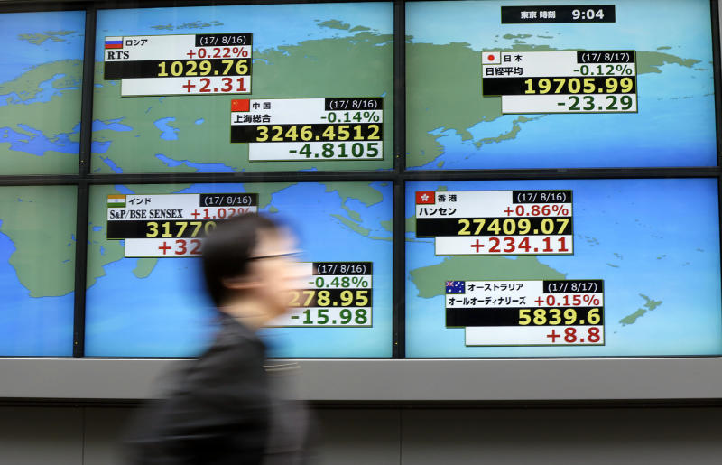 A man walks past an electronic stock board showing Japan's Nikkei 225 index, top right, and and other countries at a securities firm in Tokyo Thursday, Aug. 17, 2017. Asian shares were mostly higher Thursday, tracking gains overnight on Wall Street. The Nikkei index slipped as the yen strengthened against the U.S. dollar. (AP Photo/Eugene Hoshiko)